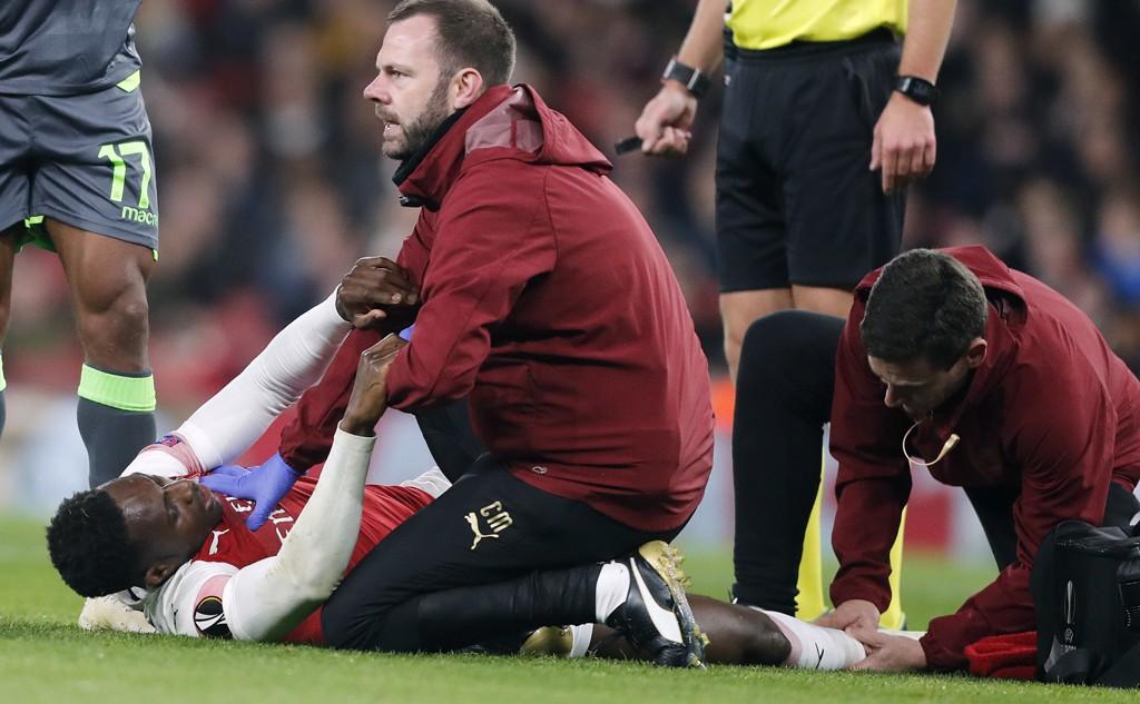 Arsenals Danny Welbeck får behandling for ankelskaden. Foto: Frank Augstein, AP / NTB scanpix