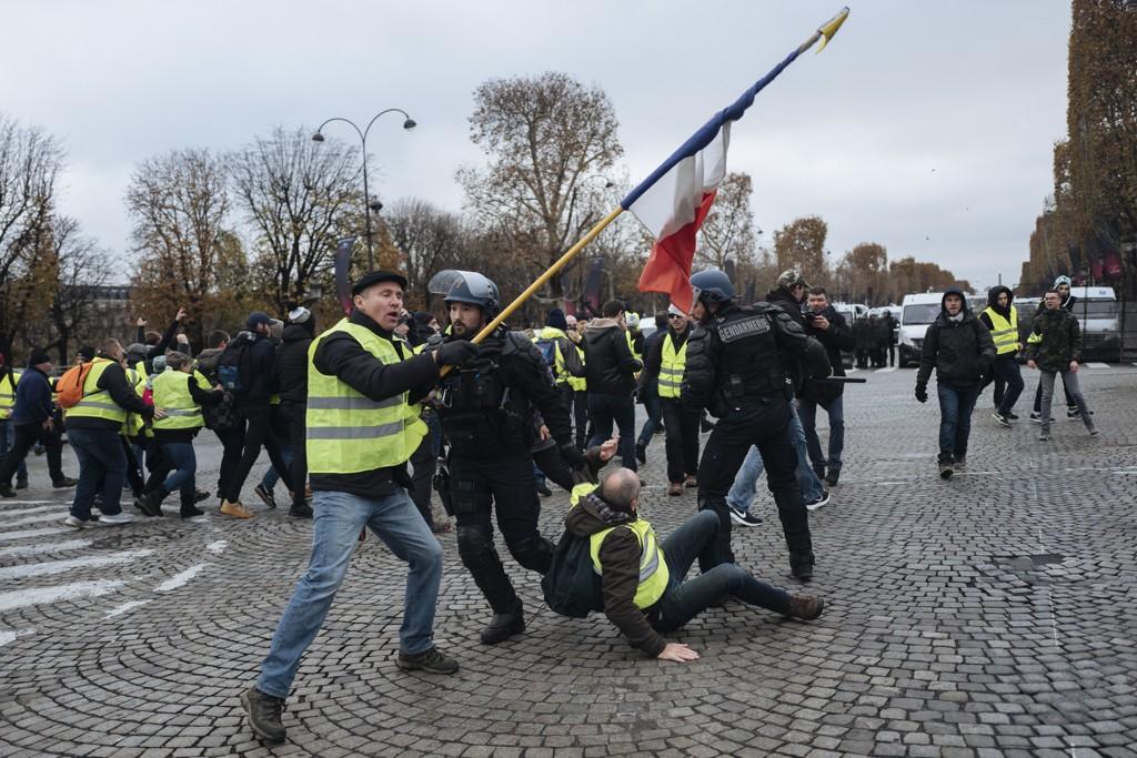 Demonstranter støtte sammen med politi i Paris lørdag. Foto: AP / NTB scanpix