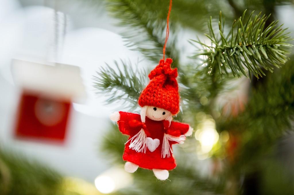 Illustrasjonsbilder av en rød nisse som henger i et juletre av plast.