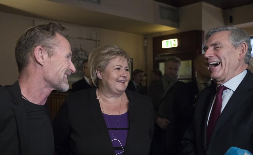 Årets Harry Hole-pris går til den tidligere britiske statsministeren Gordon Brown. Forfatter Jo Nesbø (t.v.) og statsminister Erna Solberg (H) ønsket Brown velkommen på Holes stamsted Schrøder i Oslo fredag. Foto: Terje Bendiksby / NTB scanpix