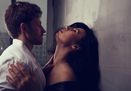Sexy couple portrait. Man in white shirt kissing his sensual beautiful girlfriend in neck with much emotion. Closeup